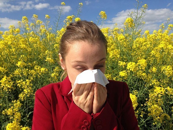 A girls is sneezing due to allergenic plants in background